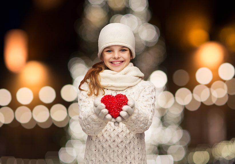 love, charity, holidays and people concept - happy girl in winter clothes with red heart over christmas tree lights background